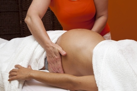 24018206 - pregnant young latina woman with beautiful skin, being wrapped with a towel, lying on a bed and having a relaxing prenatal massage, various techniques